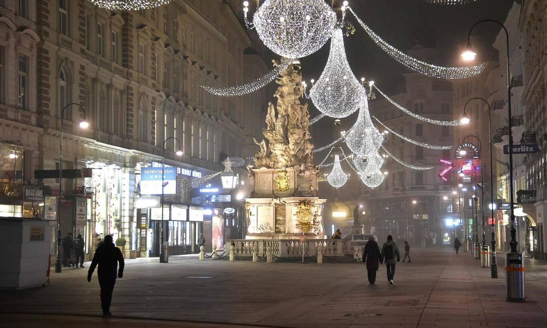 Pessoas caminham no centro da cidade quase deserta de Viena na véspera de Ano Novo, durante a nova pandemia de coronavírus. A Áustria entrou em seu terceiro bloqueio por coronavírus em 26 de dezembro até 24 de janeiro de 2021, enquanto o país batalha para reduzir sua taxa de infecção Foto: HANS PUNZ / AFP