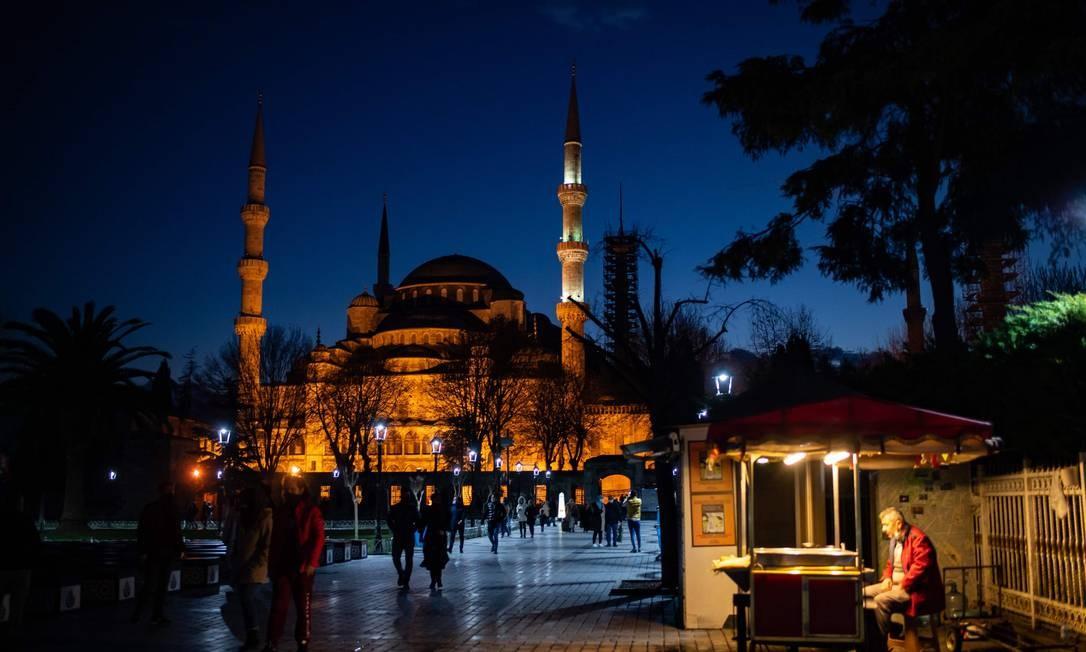 Um vendedor ambulante se senta em frente à Mesquita Azul durante as celebrações do ano novo em Istambul. O governo turco anunciou um bloqueio de quatro dias entre 31 de dezembro e 4 de janeiro de 2021 Foto: YASIN AKGUL / AFP