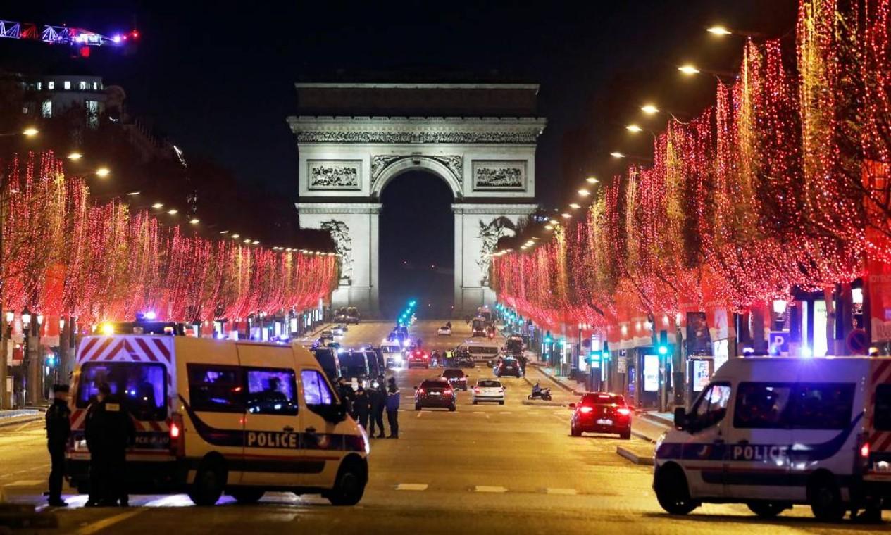 Policiais patrulham a avenida Champs Elysees, em Paris, depois que celebrações e reuniões foram proibidas devido às restrições da COVID-19 na França Foto: CHARLES PLATIAU / REUTERS