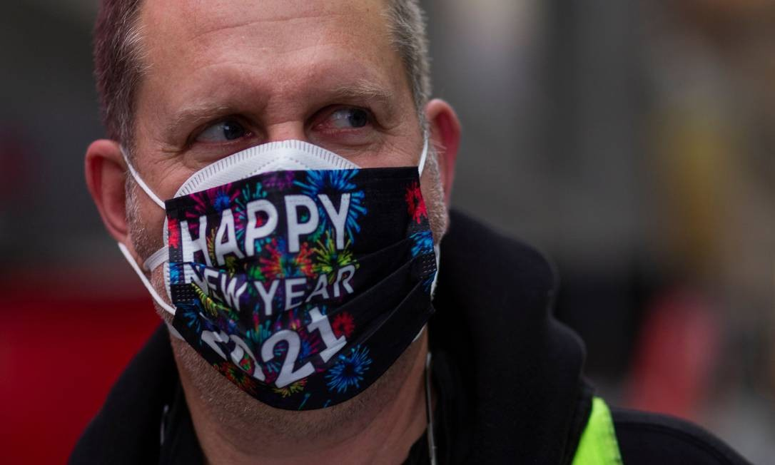 Um homem usa uma máscara facial antes da celebração da véspera de Ano Novo na Times Square de Nova York Foto: KENA BETANCUR / AFP