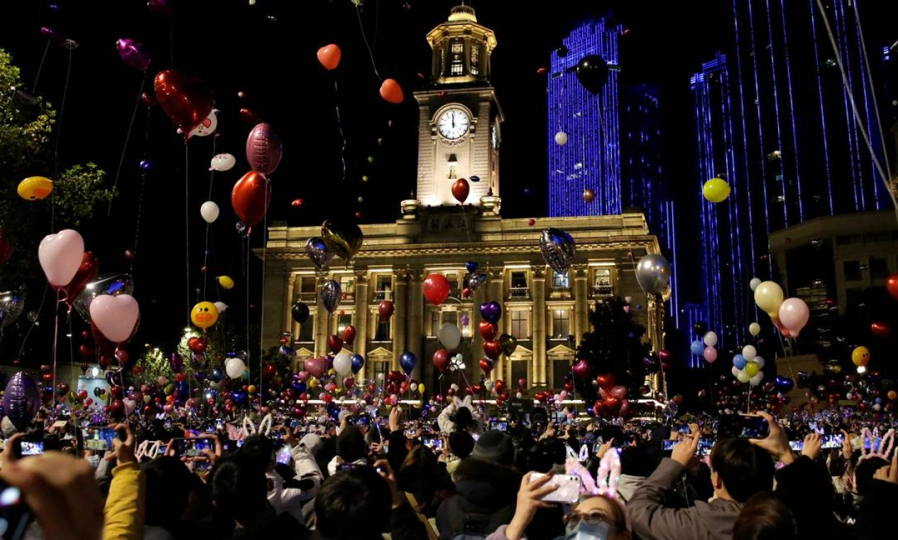 Pessoas seguram balões enquanto se reúnem para comemorar a chegada do ano novo em Wuhan, China Foto: TINGSHU WANG / REUTERS