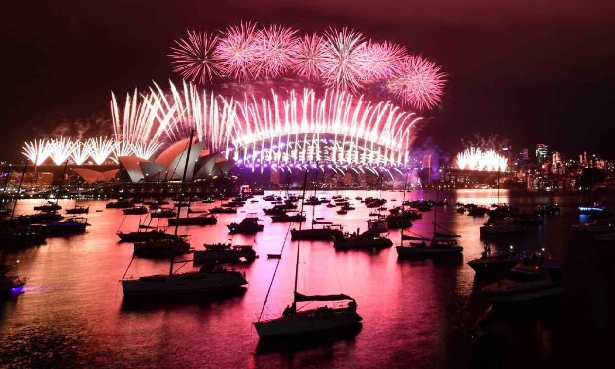 Fogos de artifício explodem na virada do ano na icônica Harbour Bridge e Opera House de Sydney, na Austrália Foto: MICK TSIKAS / AFP