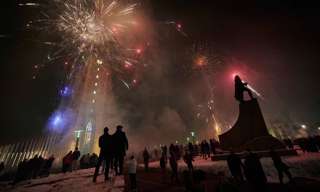 Os islandeses comemoram a chegada de 2021 com fogos de artifício iluminando o céu em Reykjavik, Islândia Foto: HALLDOR KOLBEINS / AFP