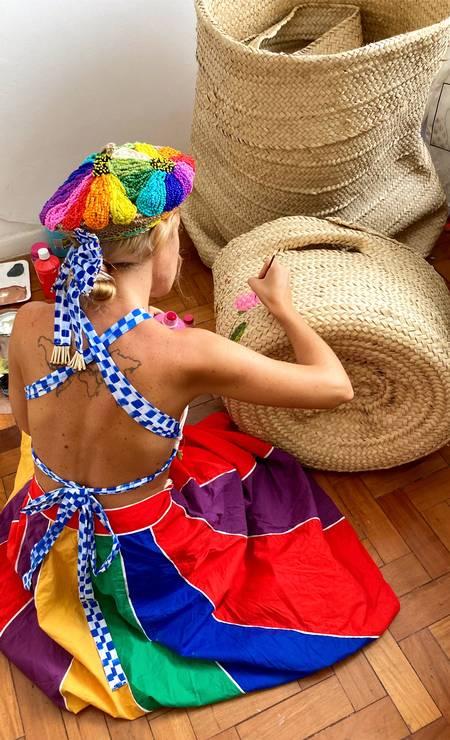 Pintando cestos e usando roupas criadas por ela Foto: Reprodução
