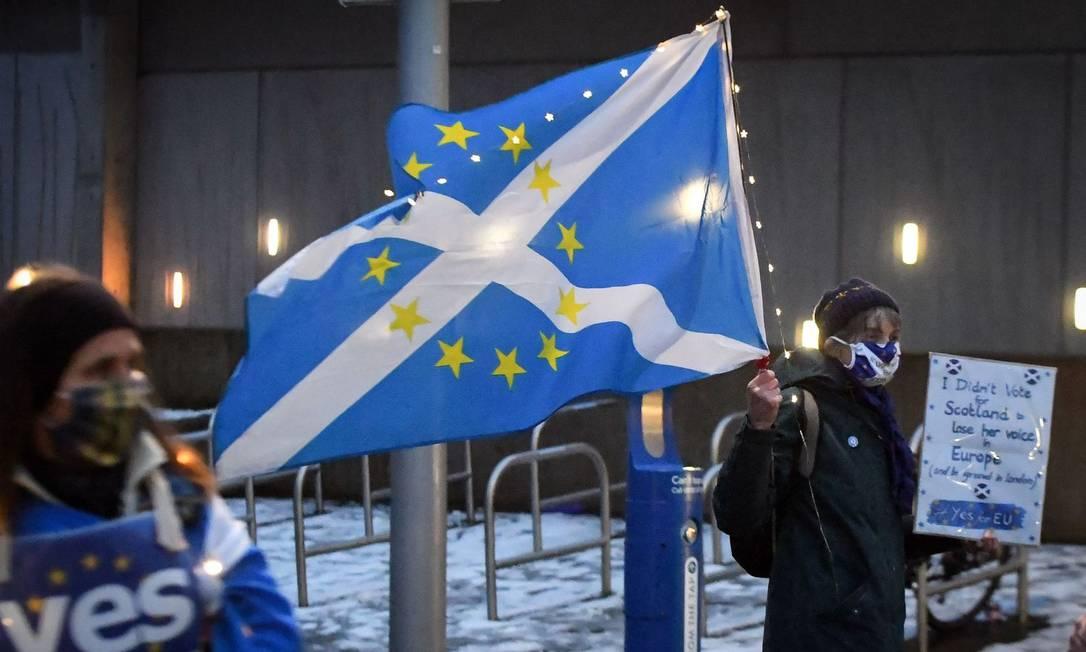 Manifestante agita uma bandeira mista da Escócia e da União Europeia em frente ao Parlamento escocês na noite de 31 de dezembro Foto: Andy Buchanan / AFP