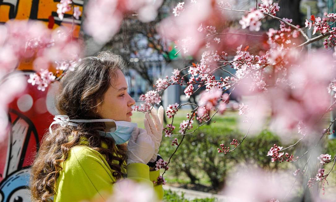 Mulher retira máscara para sentir perfume das flores em Skopje, na Macedônia do Norte Foto: OGNEN TEOFILOVSKI / Reuters
