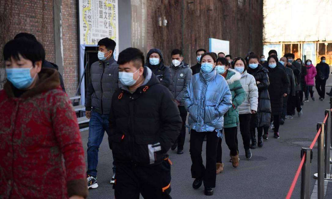 Pessoas formam fila em centro de vacinação contra a Covid-19 em Pequim, na China, nesta segunda-feira (4) Foto: GREG BAKER / AFP