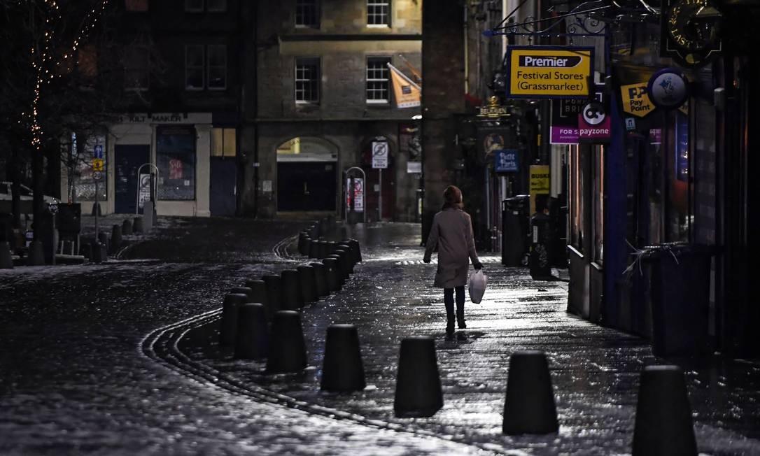 Pedestre caminha sozinho no centro de Edimburgo, na Escócia, durante o Ano Novo Foto: Andy Buchanan / AFP