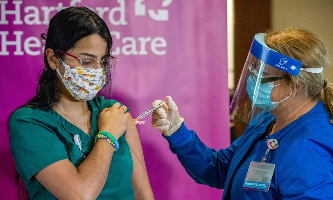 Profissional de saúde recebe vacina da Covid-19 em Connecticut, Estados Unidos Foto: JOSEPH PREZIOSO / AFP