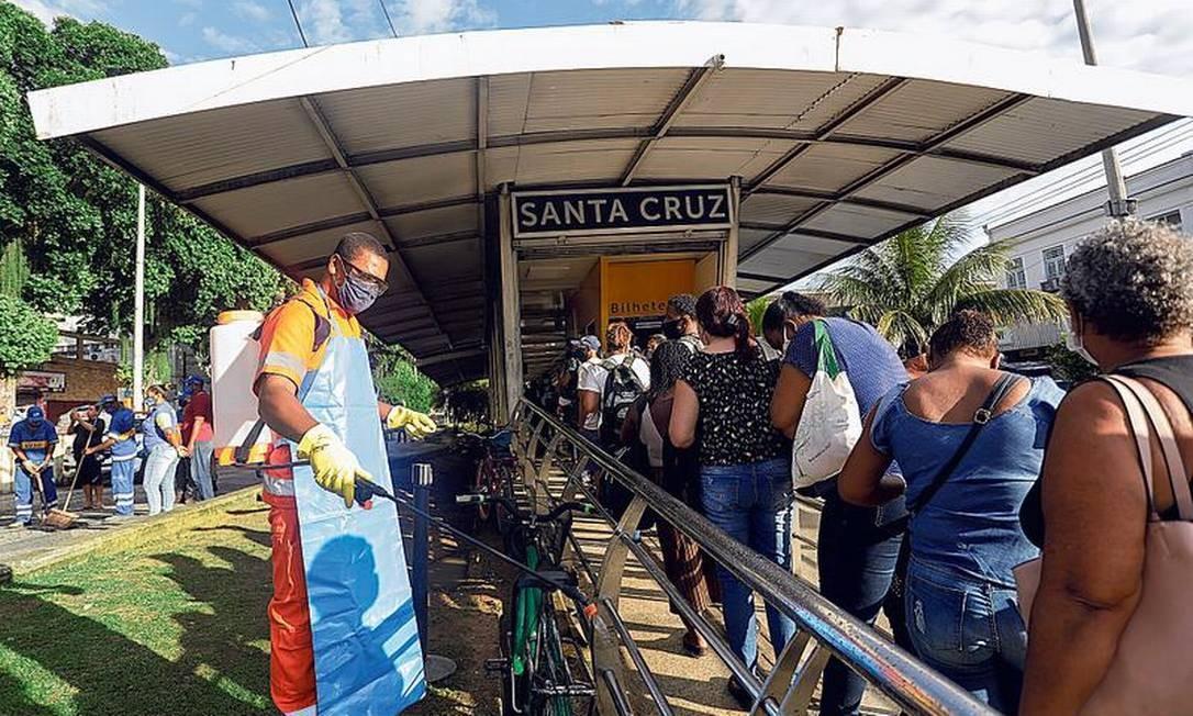 Funcionário da Comlurb faz a desinfecção na estação Santa Cruz, no primeiro dia útil do ano, a fila para embarcar já dava volta no quarteirão às 5h Foto: Gabriel de Paiva / Agência O Globo
