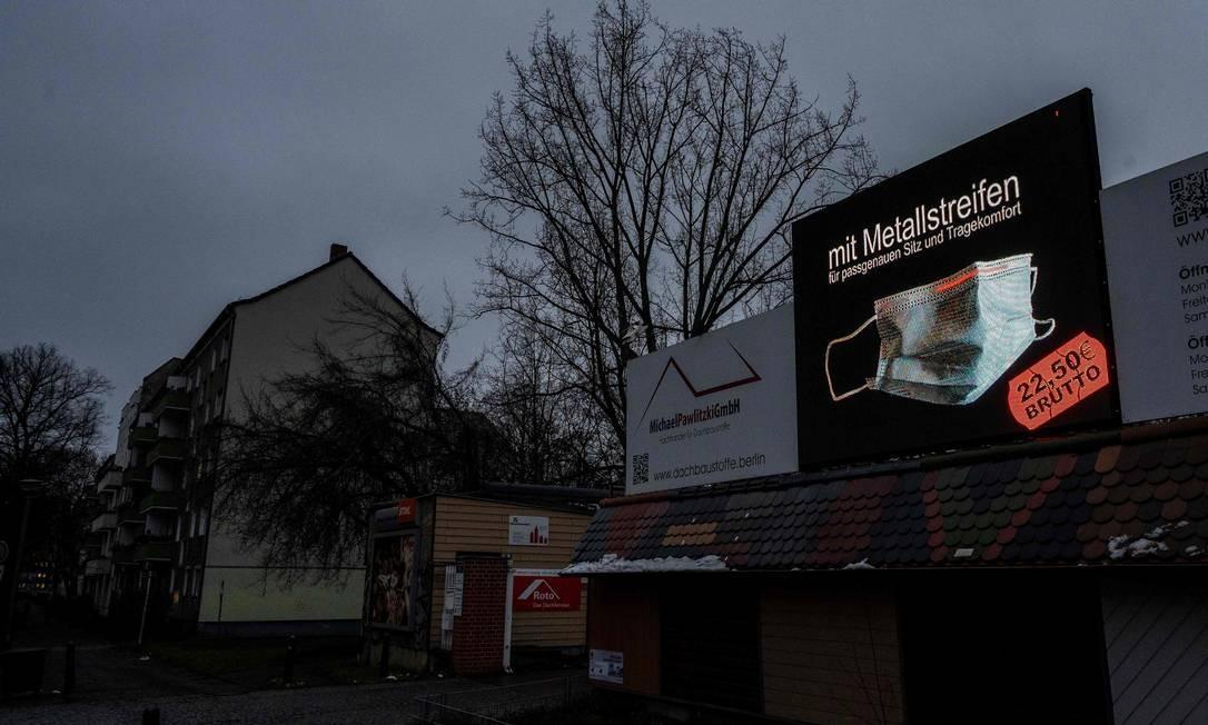 Em rua vazia com estabelecimentos fechados, outdoor exibe uma máscara à venda na Alemanha Foto: JOHN MACDOUGALL / AFP