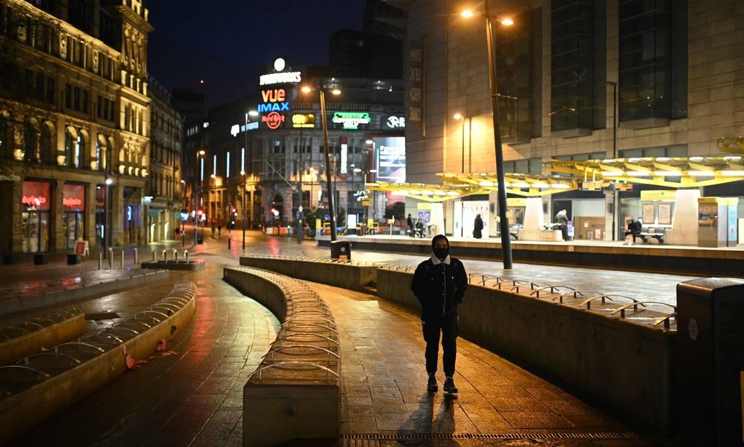 Homem caminha por uma rua quase deserta no centro de Manchester, noroeste da Inglaterra, quando a Grã-Bretanha entra em um bloqueio nacional para combater a disseminação do COVID-19 Foto: OLI SCARFF / AFP