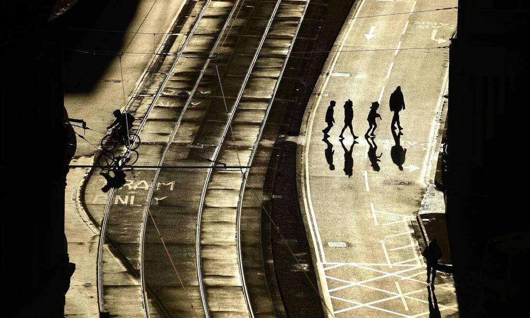 Pedestres atravessam uma rua vazia em Manchester, nesta terça-feira (5). Bloqueio de seis semanas da Inglaterra, que começou à meia-noite, é semelhante ao da primeira restrição nacional de coronavírus, em março do ano passado Foto: OLI SCARFF / AFP