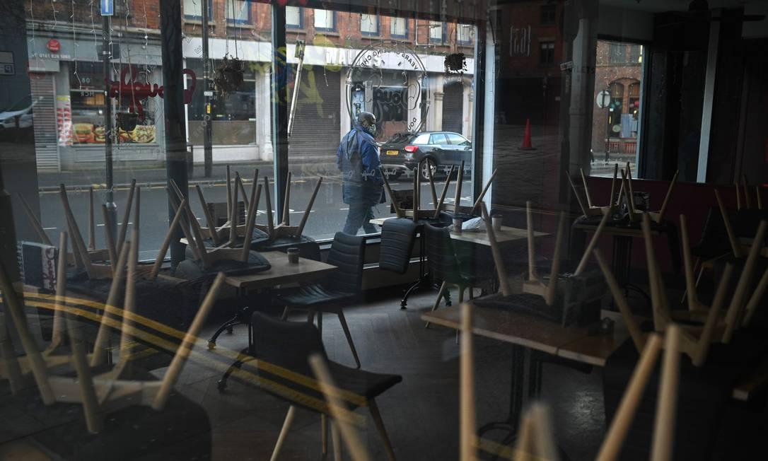 Homem passa por um café fechado em Manchester. Bares e restaurantes já estavam fechados, e as determinações para reuniões sociais também já eram bem restritas Foto: OLI SCARFF / AFP
