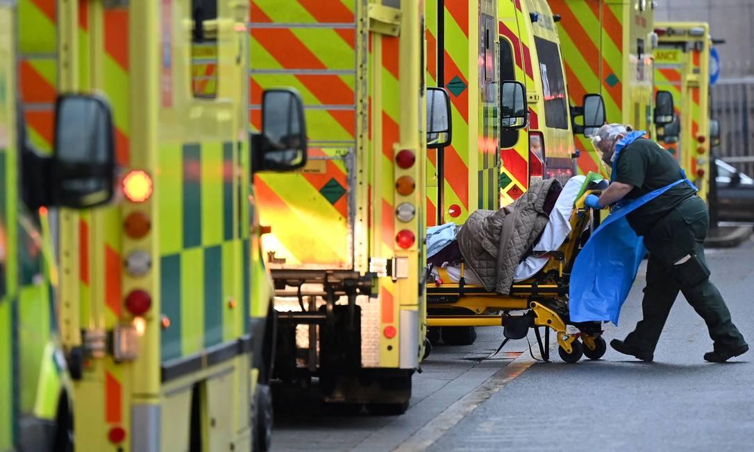Paramédico é visto entre ambulâncias do lado de fora do Royal London Hospital, no leste de Londres. Disseminação da Covid-19 está acelerando nos países com o avanço de uma cepa mais transmissível do coronavírus Foto: JUSTIN TALLIS / AFP