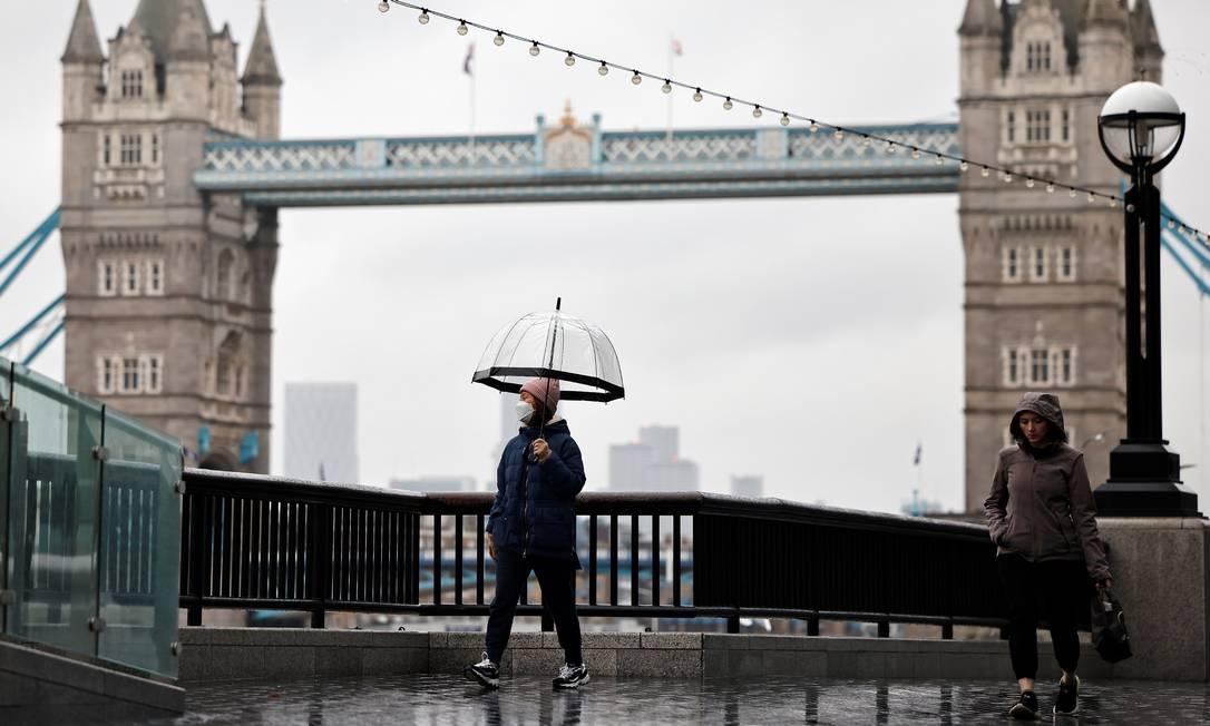 Pedestres caminham ao longo do dique, perto da Tower Bridge, enquanto a Grã-Bretanha entra em um bloqueio nacional, em Londres. População só poderá sair de casa para fazer compras essenciais, praticar exercícios, para trabalhar caso seja impossível fazê-lo de casa e em outras poucas exceções Foto: TOLGA AKMEN / AFP