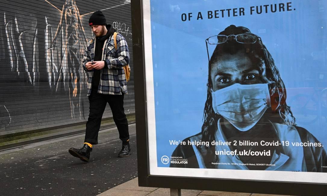 Pedestre passa por um pôster da Unicef, promovendo as vacinas da Covid-19, em Manchester Foto: OLI SCARFF / AFP