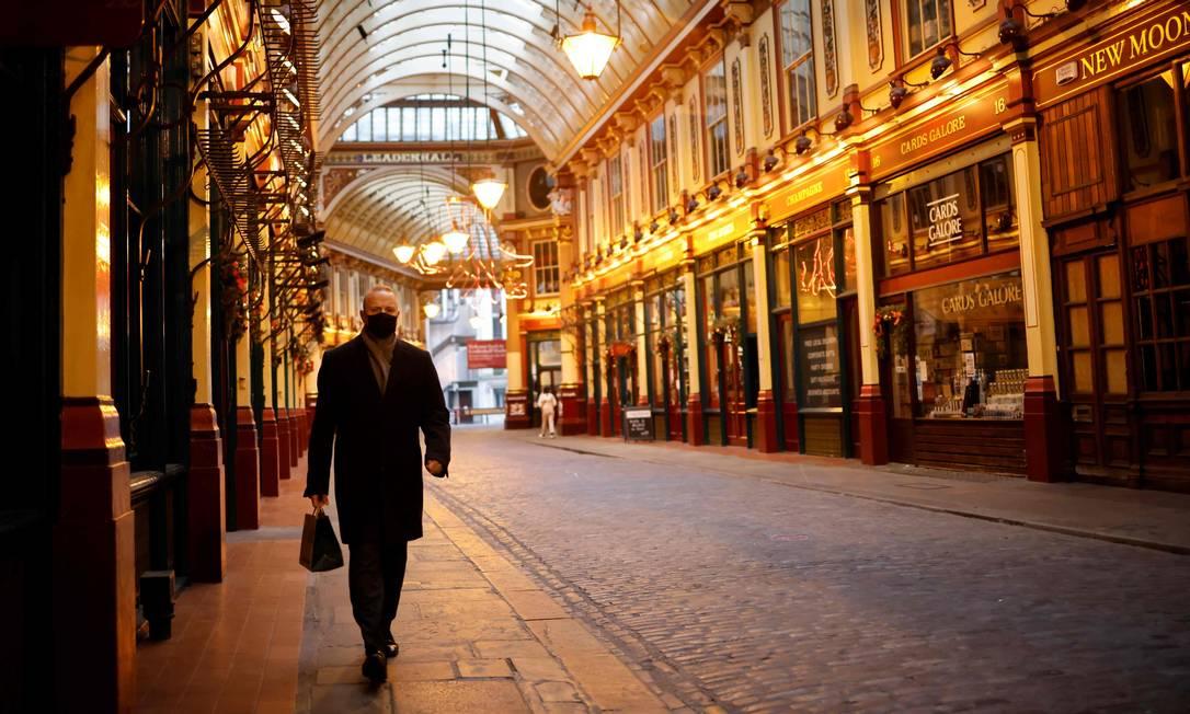Um pedestre solitário caminha pelo mercado Leadenhall, na cidade de Londres, completamente vazio Foto: TOLGA AKMEN / AFP