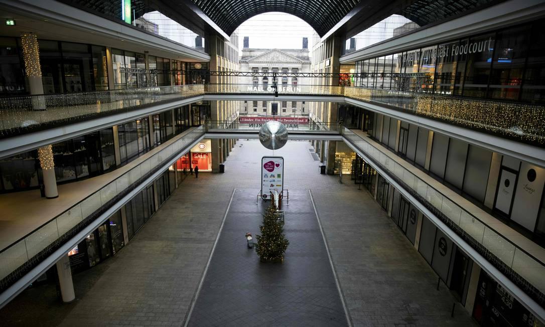 """Um pedestre solitário é visto no """"Mall of Berlin"""", o maior shopping center da capital alemã. No país, além de estender o prazo da quarentena até o fim de janeiro, os moradores das regiões onde há maior propagação do vírus terão as viagens não essenciais restritas a um raio de 15 km Foto: ODD ANDERSEN / AFP"""