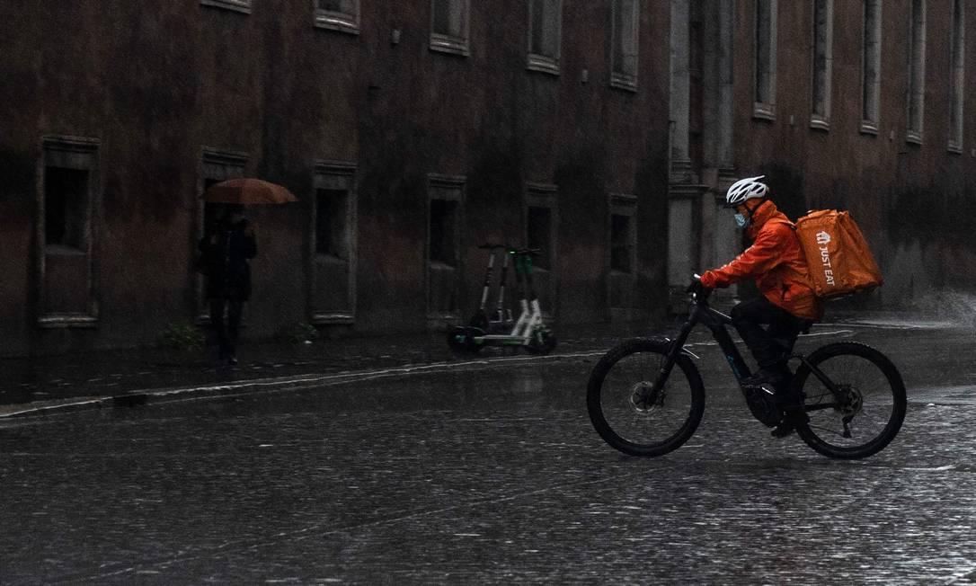 Um ciclista de entrega de comida pedala na chuva no centro de Roma. Itália também tomou decisões semelhantes um dia após Inglaterra e Escócia anunciarem o retorno a uma quarentena total Foto: TIZIANA FABI / AFP