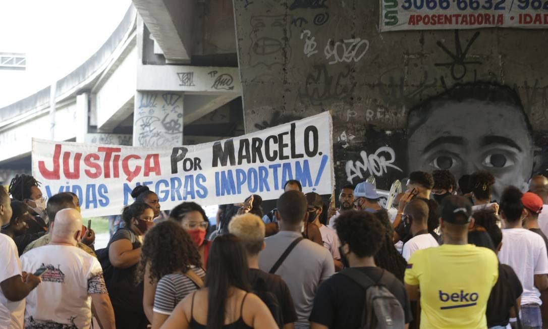 Faixa pede justiça por Marcelo. Ao fundo, grafite feito em sua homenagem, no local da tragédia Foto: Domingos Peixoto / Agência O GLOBO