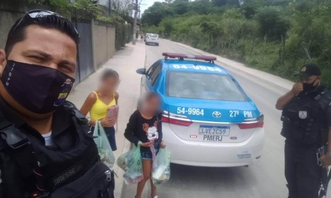 PMs e as crianças com as compras na porta de casa em Guaratiba Foto: PMERJ / Divulgação PMERJ