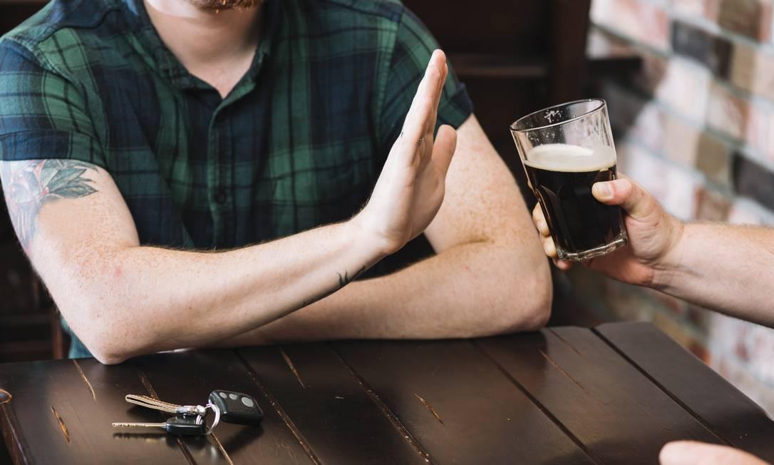 Homem recusa um copo de rum oferecido por amigo. Foto: Freepik