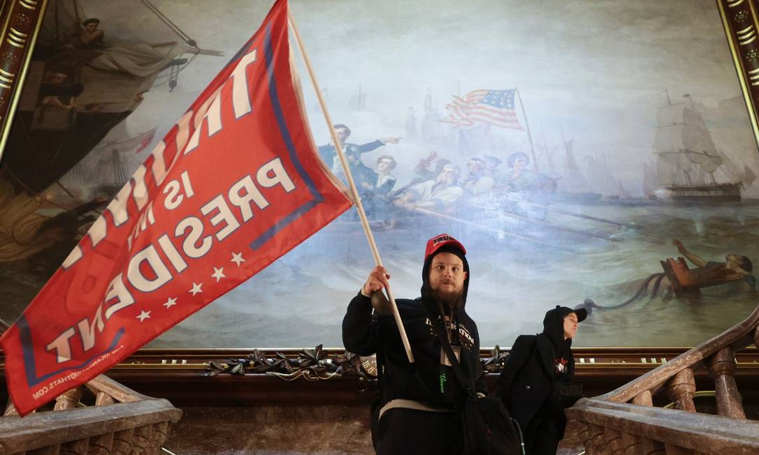 Um manifestante segura uma bandeira de apoio ao presidente Trump dentro do edifício do Capitólio dos EUA, perto da Câmara do Senado Foto: WIN MCNAMEE / AFP