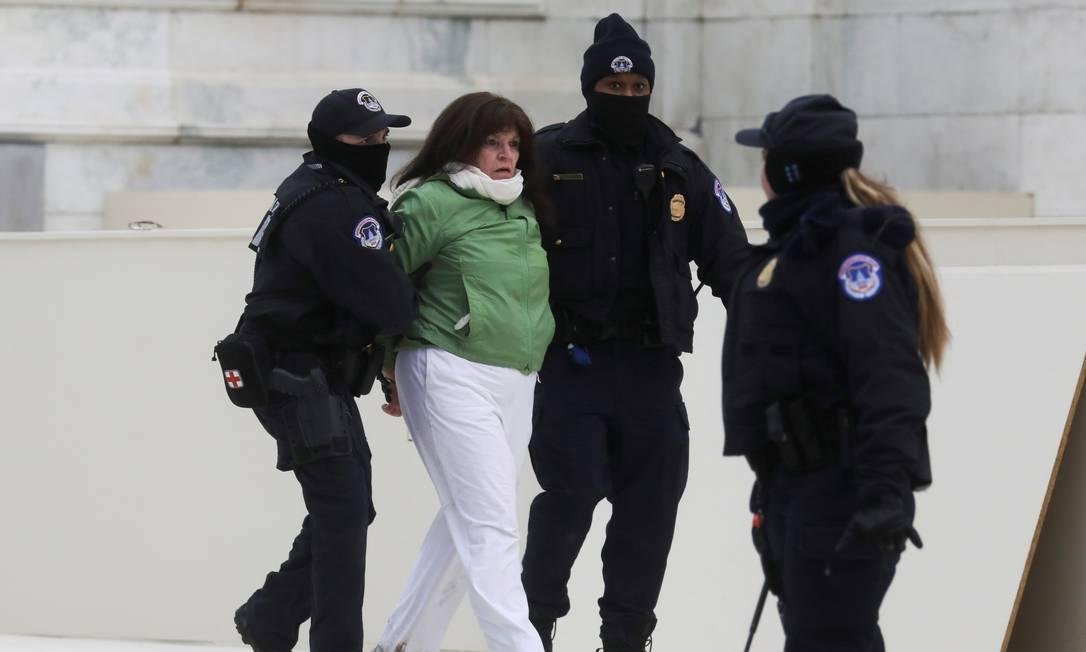 Policiais detêm uma mulher após um confronto com simpatizantes do presidente dos Estados Unidos, Donald Trump, do lado de fora do Congresso americano durante sessão de confirmação da vitória do democrata Joe Biden Foto: LEAH MILLIS / REUTERS