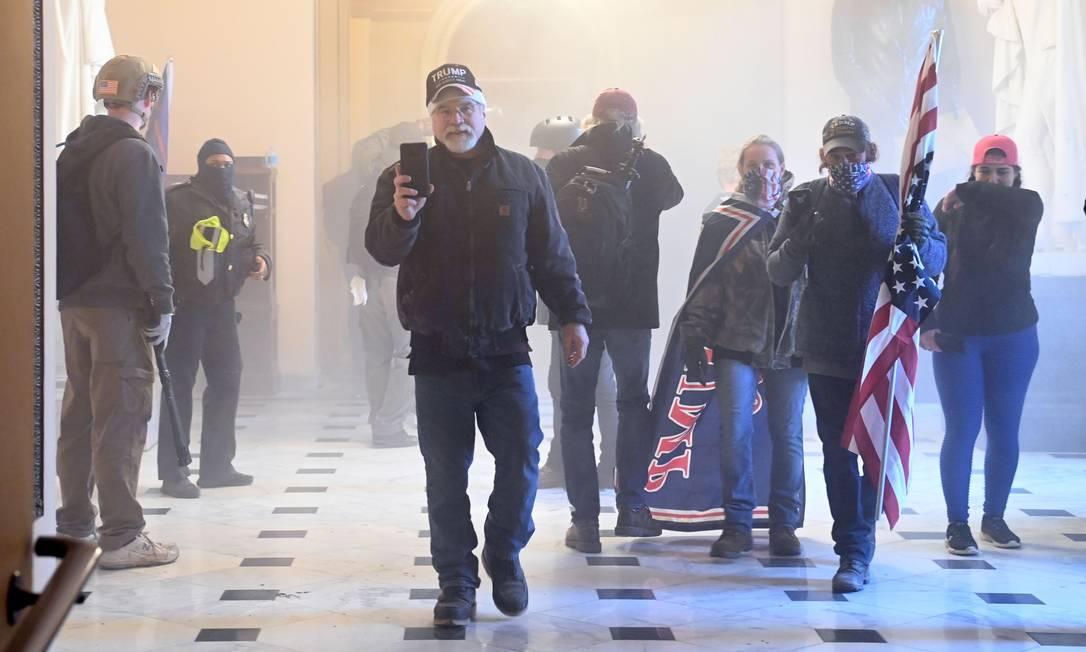 Apoiadores do presidente Donald Trump entram no Capitólio enquanto gás lacrimogêneo lançado pela polícia toma o corredor do prédio Foto: SAUL LOEB / AFP