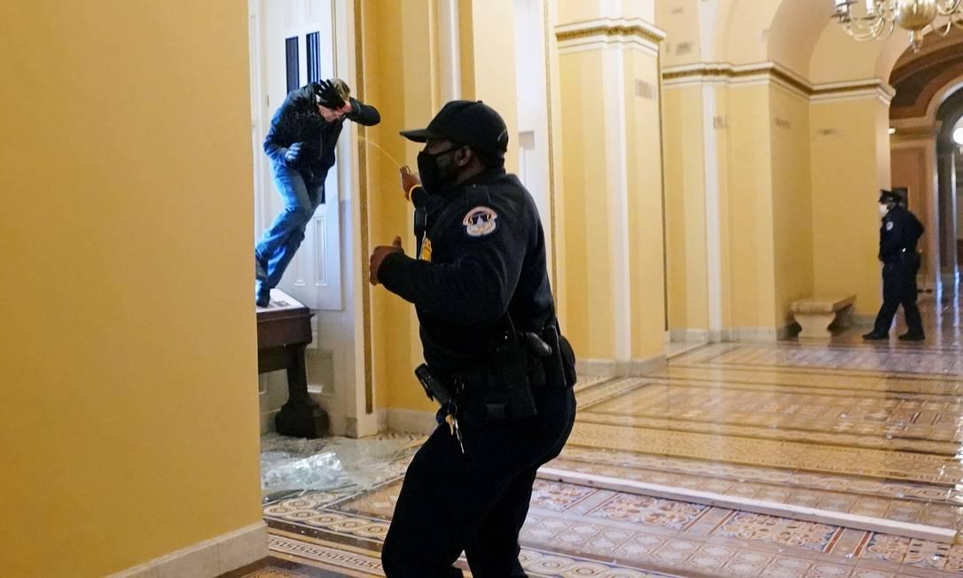 Um policial do Capitólio atira spray de pimenta em um manifestante que tenta entrar no prédio do Congresso Foto: POOL / REUTERS