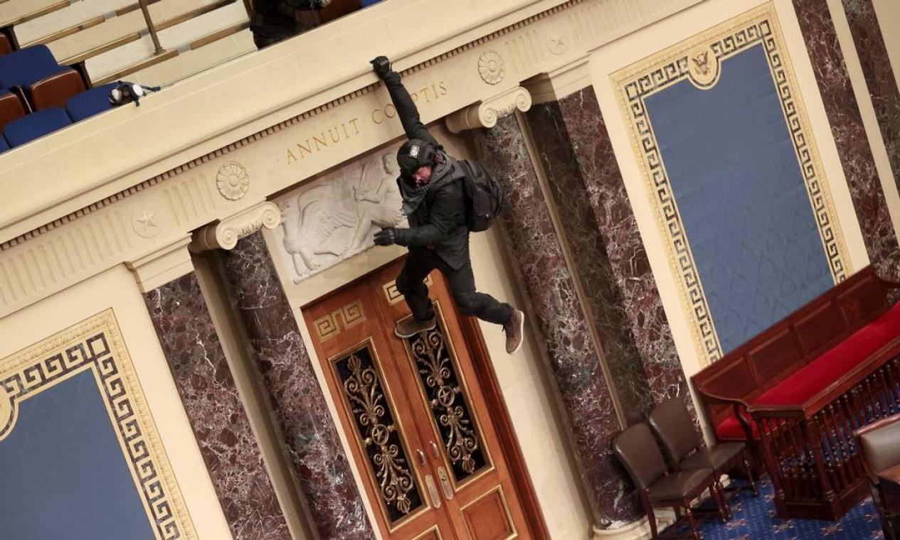 Um manifestante é visto pendurado na varanda do pelnário do Senado Foto: WIN MCNAMEE / AFP