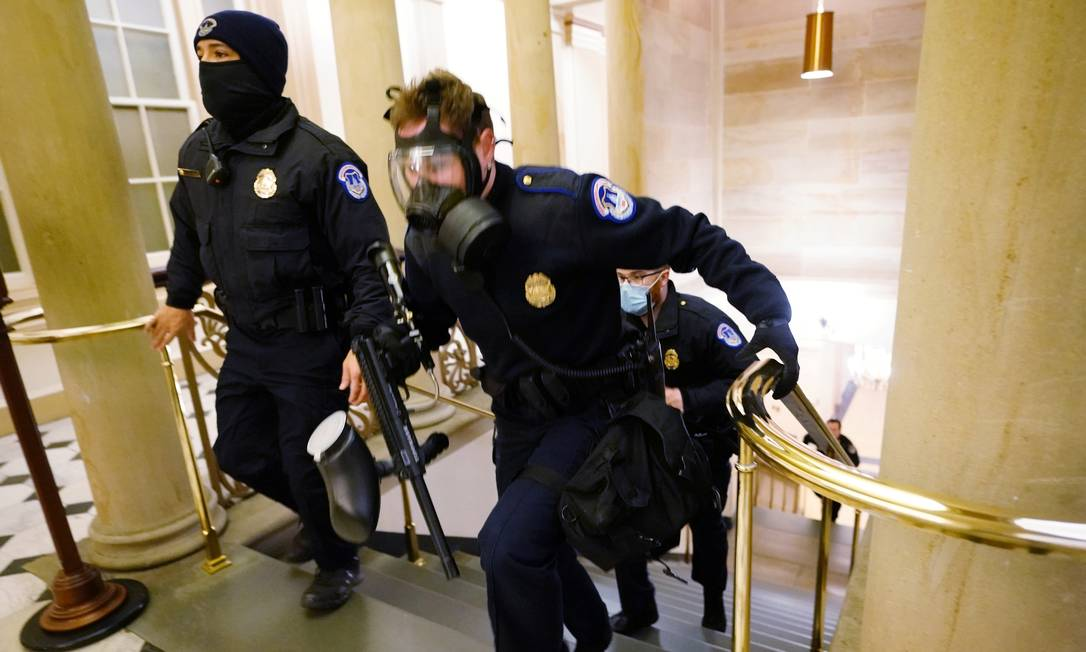 Policiais do Capitólio tomam posições enquanto os manifestantes invadem o prédio Foto: POOL / REUTERS