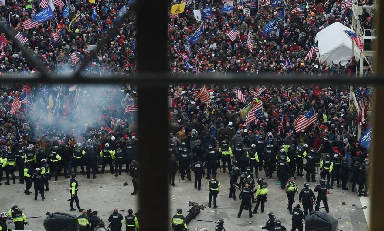 A polícia segura os apoiadores do presidente dos EUA, Donald Trump, enquanto eles se reúnem em frente à Rotunda do Capitólio dos EUA Foto: OLIVIER DOULIERY / AFP