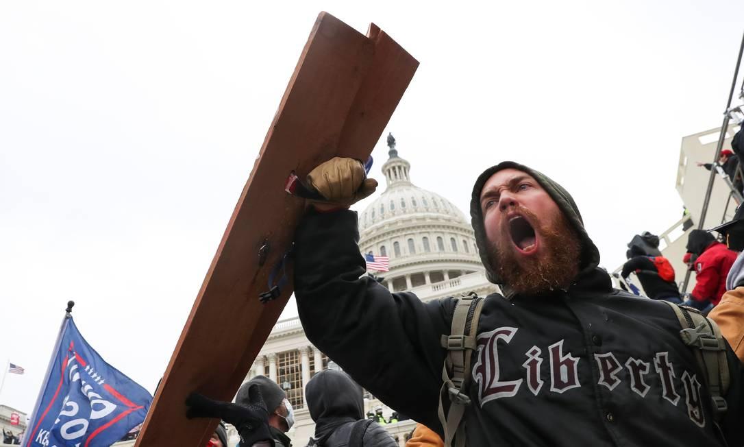 Um homem grita enquanto apoiadores de Trump se reúnem em frente ao prédio do Congresso Foto: LEAH MILLIS / REUTERS