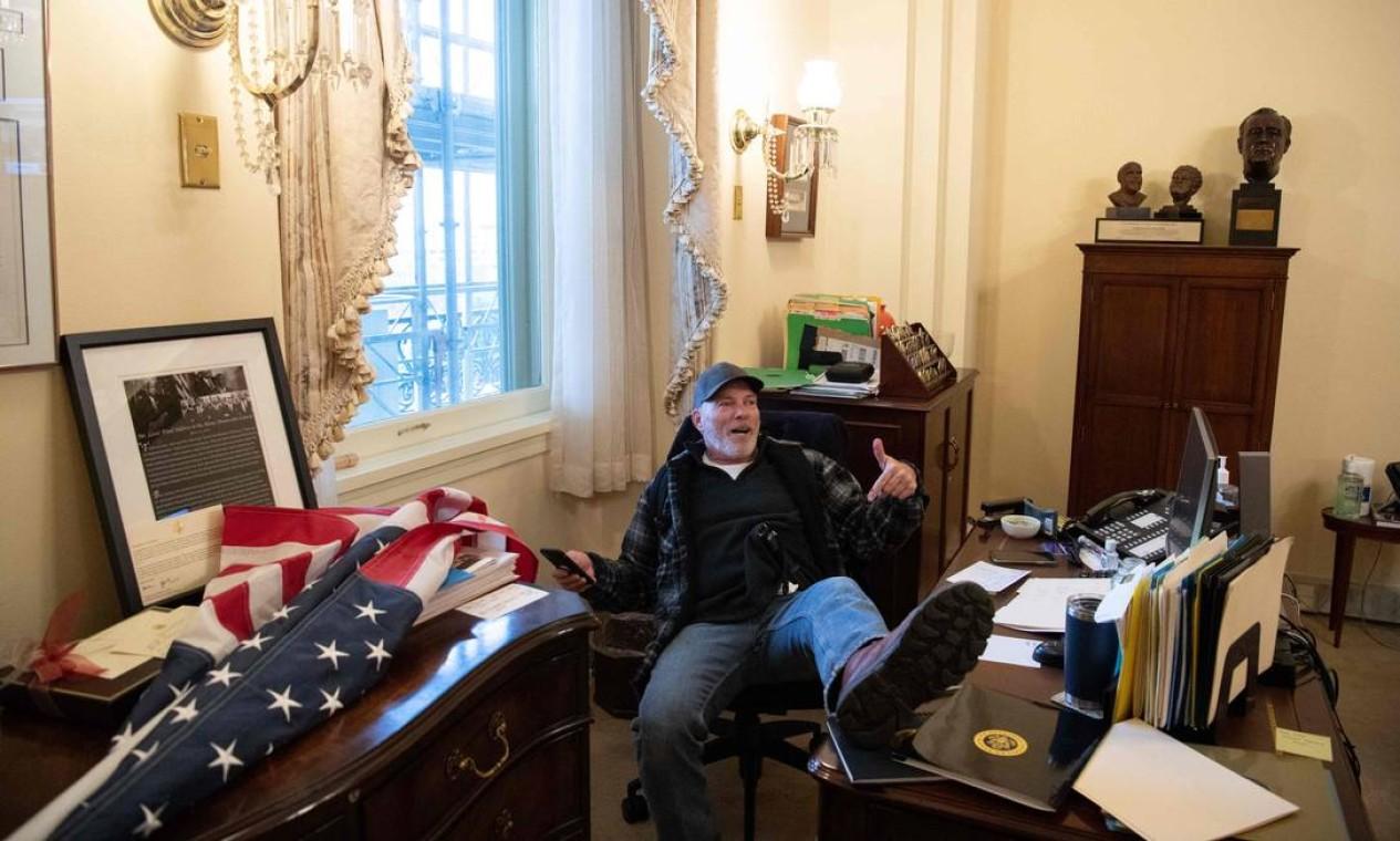 Um manifestante senta-se no gabinete da presidente da Câmara, Nancy Pelosi, durante invasão ao prédio do Capitólio Foto: SAUL LOEB / AFP