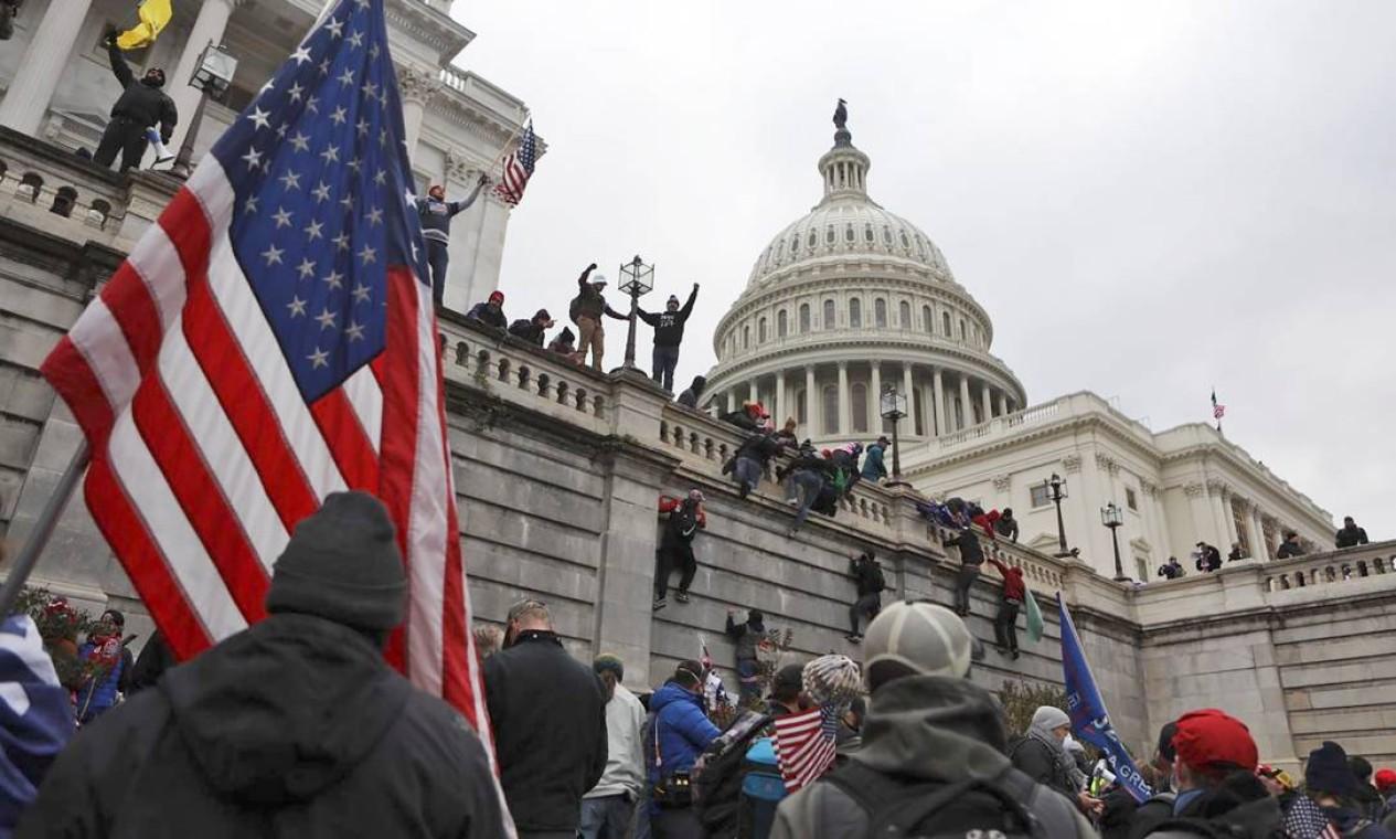 Apoiadores de Donald Trump escalam as paredes do Capitólio dos EUA, em Washington Foto: JIM URQUHART / REUTERS