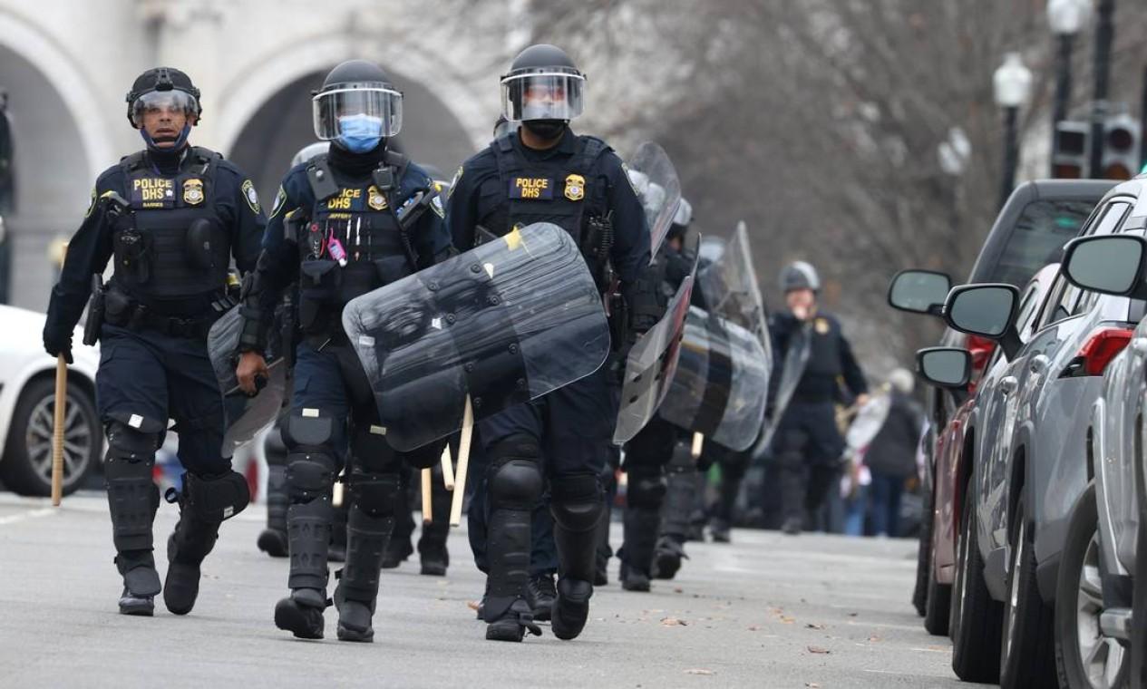 Policiais em traje antimotim caminham em direção ao Capitólio dos EUA enquanto os manifestantes invadem o prédio Foto: TASOS KATOPODIS / AFP
