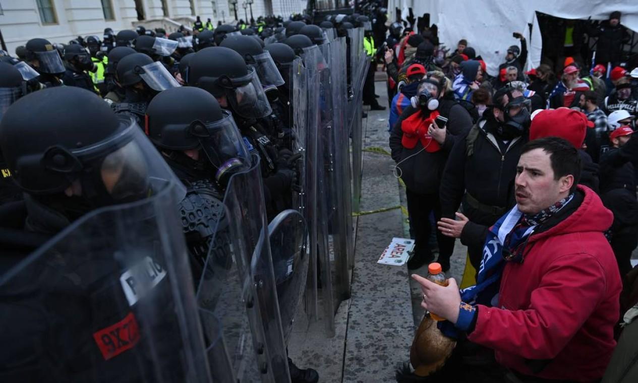 Apoiadores de Donald Trump confrontam policiais do lado de fora do Congresso americano Foto: BRENDAN SMIALOWSKI / AFP