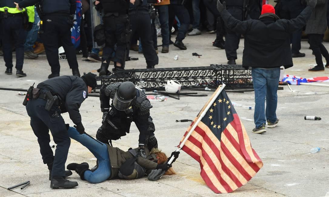 A polícia detém um manifestante durante protesto pró-Trump em frente ao Congresso amerciano Foto: ROBERTO SCHMIDT / AFP