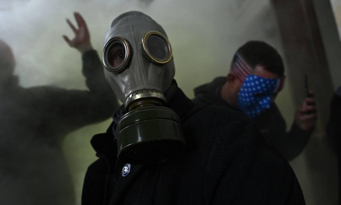 Apoiador de Trump usa uma máscara de gás enquanto invade o Congresso americano Foto: BRENDAN SMIALOWSKI / AFP