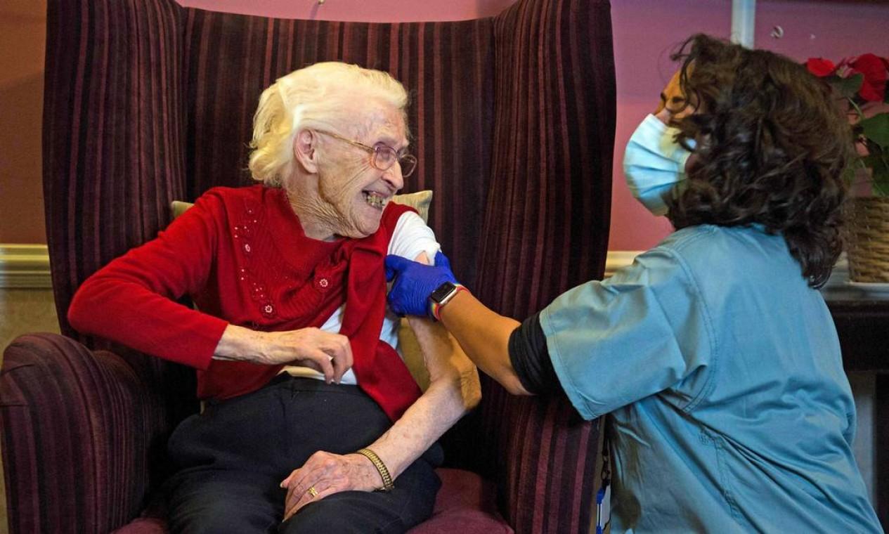 Ellen Prosser, de cem anos, conhecida como Nell, recebe a vacina Oxford / AstraZeneca COVID-19 no Sunrise Care Home, em Sidcup, sudeste de Londres, Inglaterra Foto: KIRSTY O'CONNOR / AFP