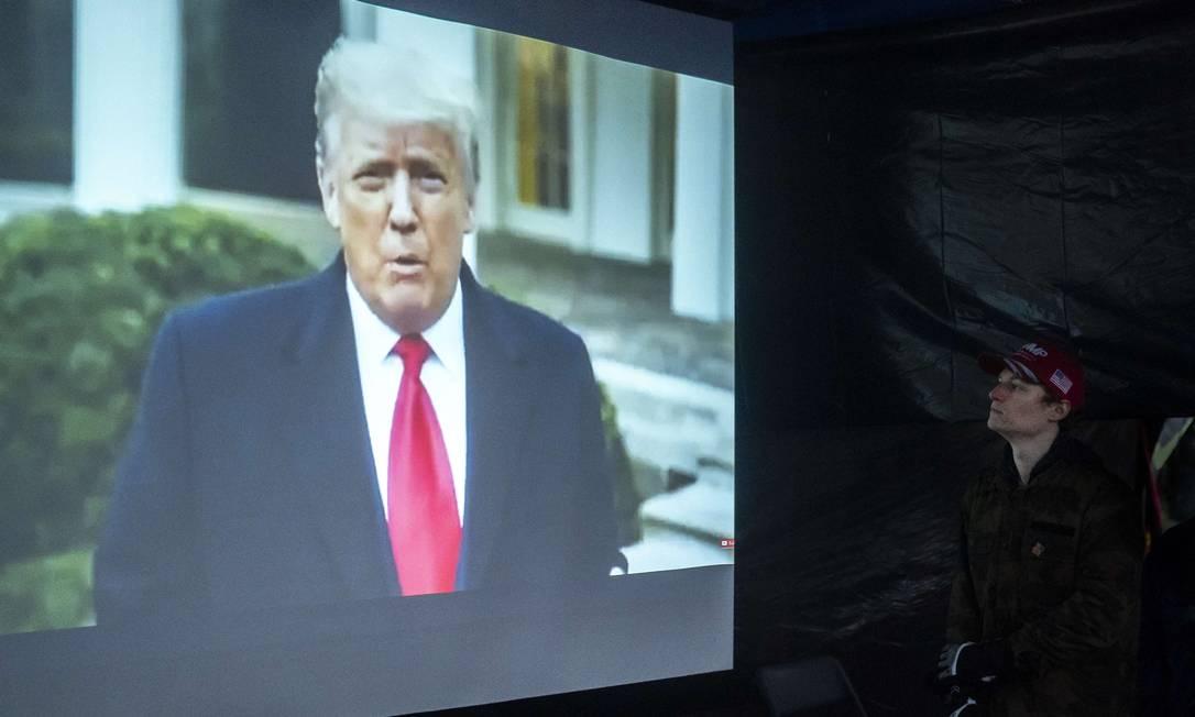 Apoiador de Donald Trump no estado do Oregon assiste a mensagem do presidente depois de invasão do Capitólio. Vídeo acabou removido das principais plataformas Foto: Nathan Howard / AFP