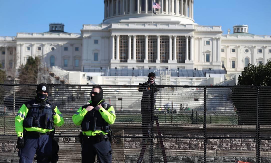 Policiais patrulham as áreas próximas ao Capitólio, enquanto cercas de proteção são erguidas na região Foto: JOE RAEDLE / AFP