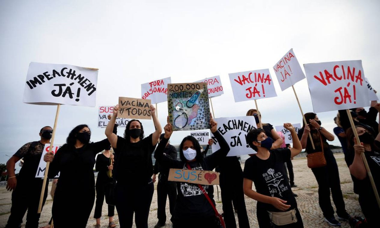 Vestidos de preto em sinal de luto, manifestantes exibem cartazes em que pedem o impeachment do presidente e vacina contra a Covid-19 Foto: ADRIANO MACHADO / REUTERS