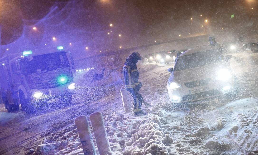 Bombeiros ajudam motoristas presos no anel viário M30 em Madrid, devido a uma forte tempestade de neve que atingiu grande parte da Espanha Foto: OSCAR DEL POZO / AFP