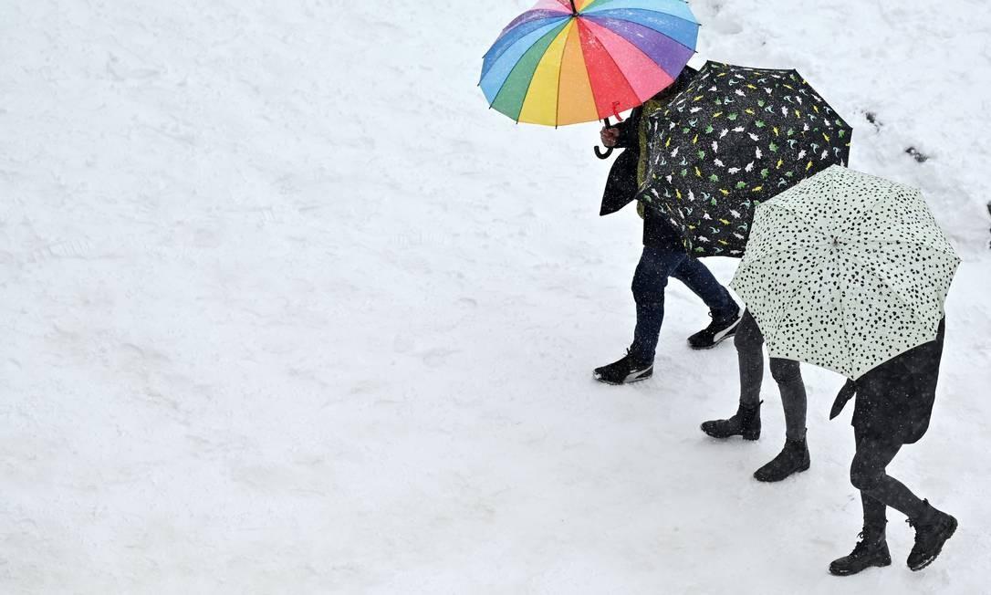 Pessoas usando guarda-chuvas caminham pela neve Foto: GABRIEL BOUYS / AFP