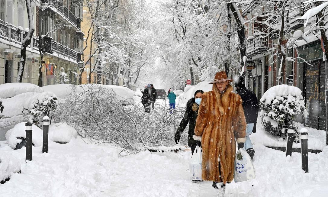 Mulher vestindo casaco de pele caminha em meio a forte nevasca em Madrid Foto: GABRIEL BOUYS / AFP