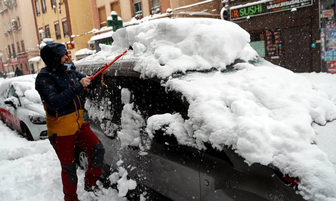 Homem remove grande quantidade de neve acumulada em cima de carro estacionado Foto: SUSANA VERA / REUTERS