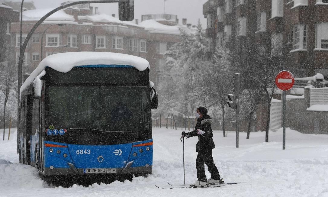 Mulher passa de esquis por um ônibus preso em uma rua em meio a uma forte nevasca em Madrid Foto: PIERRE-PHILIPPE MARCOU / AFP